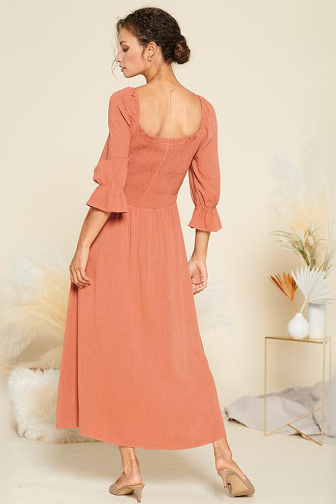 Back side of a rust peasant dress with side slit.
