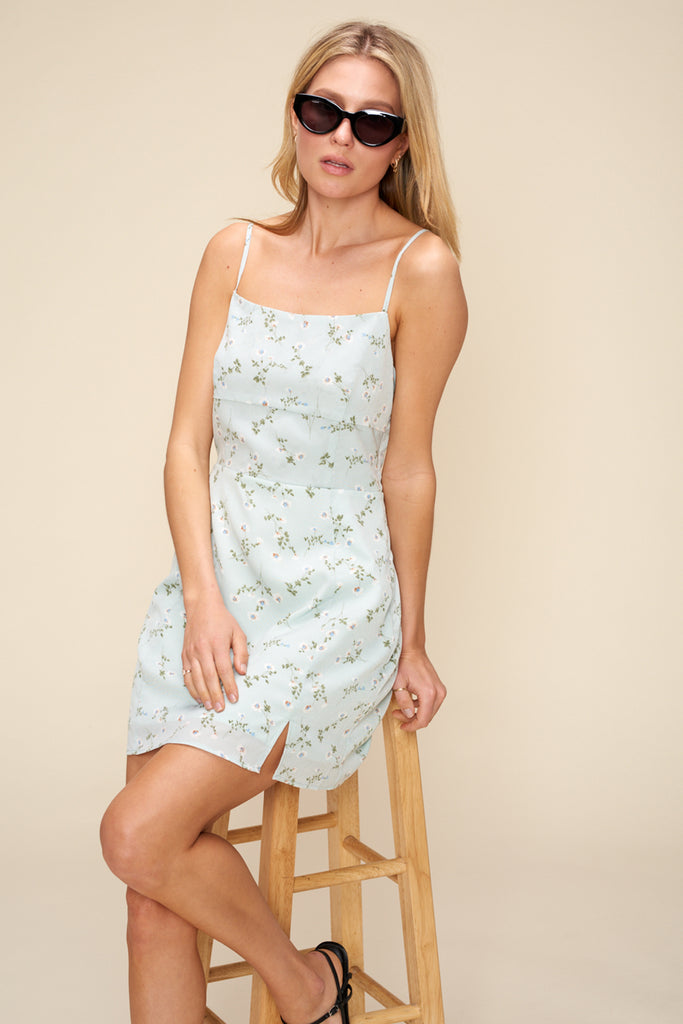 A woman wearing a light blue ditsy floral mini dress.