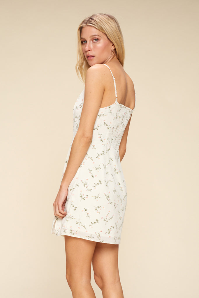 Back side of an ivory ditsy floral mini dress.