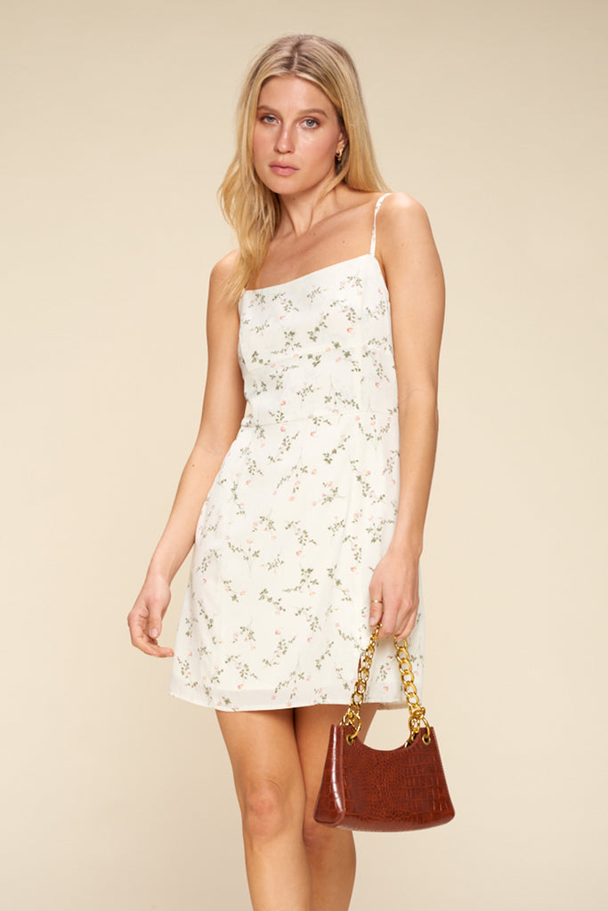 A woman wearing an ivory ditsy floral mini dress.