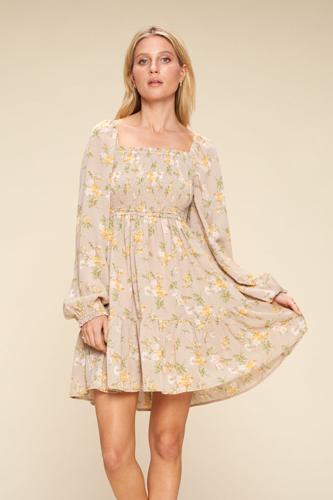 A woman wearing a sand floral tiered mini dress.