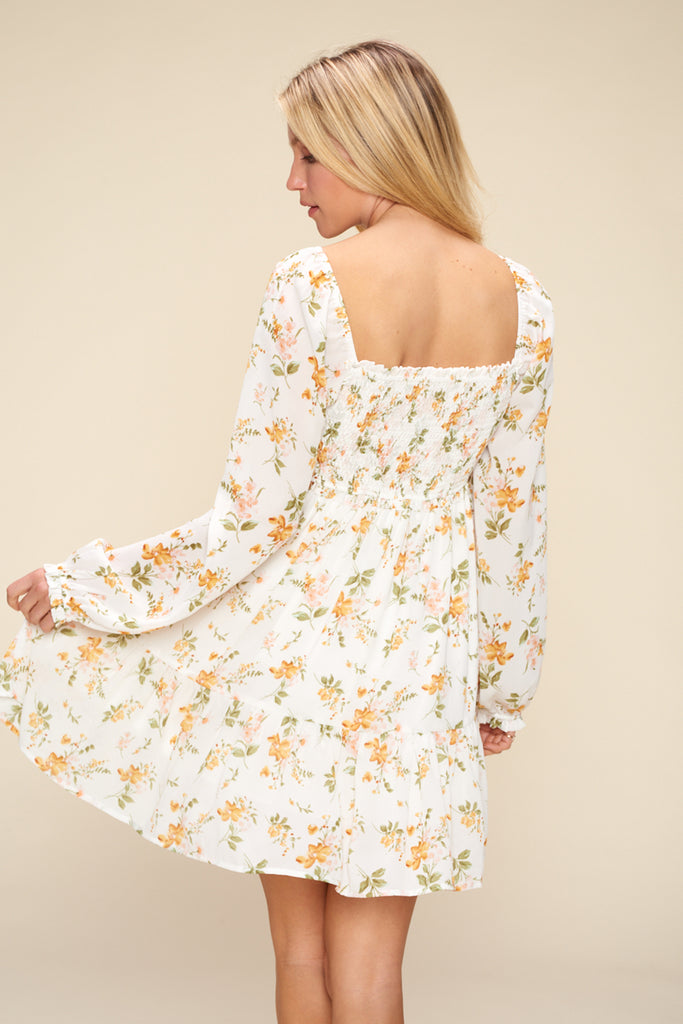 Back side of an ivory floral tiered mini dress.