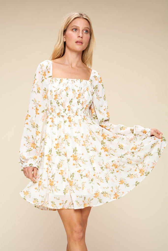 A woman wearing an ivory floral tiered mini dress.