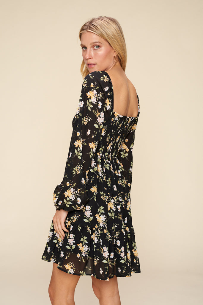 Back side of a black floral tiered mini dress.