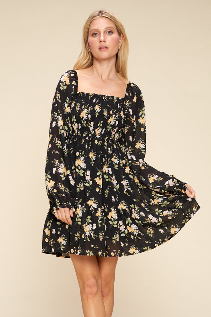 A woman wearing a black floral tiered mini dress.