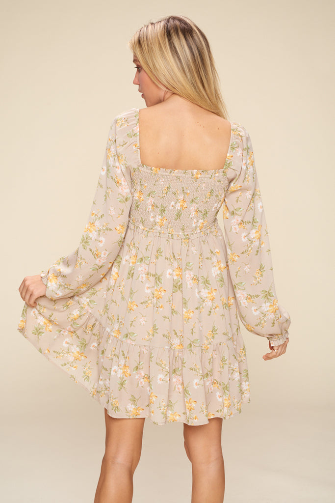 Back side of a sand floral tiered mini dress.
