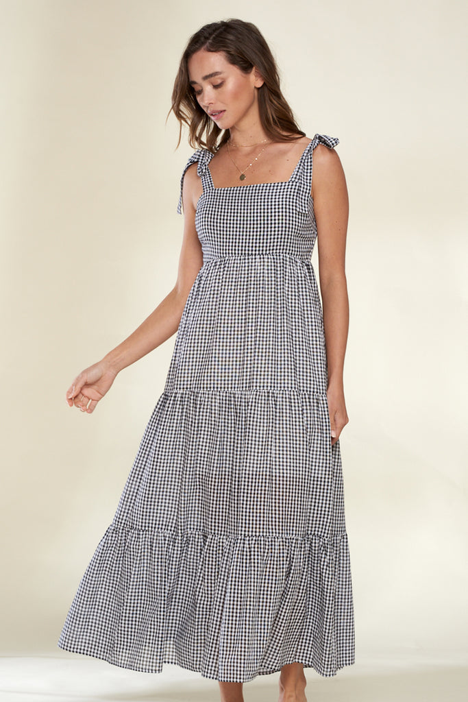 A woman wearing a black tiered gingham midi dress.