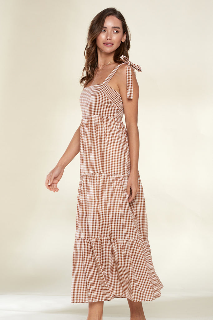 A woman wearing a brown tiered gingham midi dress.