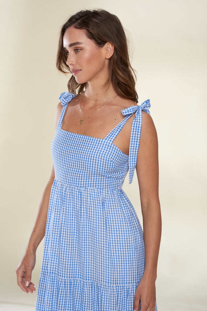 A close up of light blue tiered gingham midi dress.
