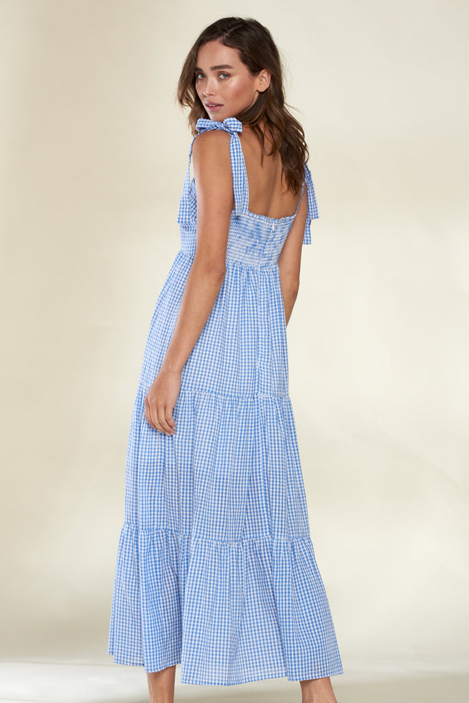 Back side of a light blue tiered gingham midi dress.