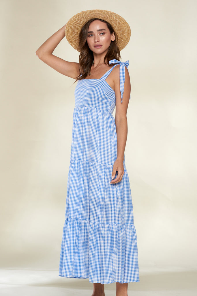 A woman wearing a light blue tiered gingham midi dress.