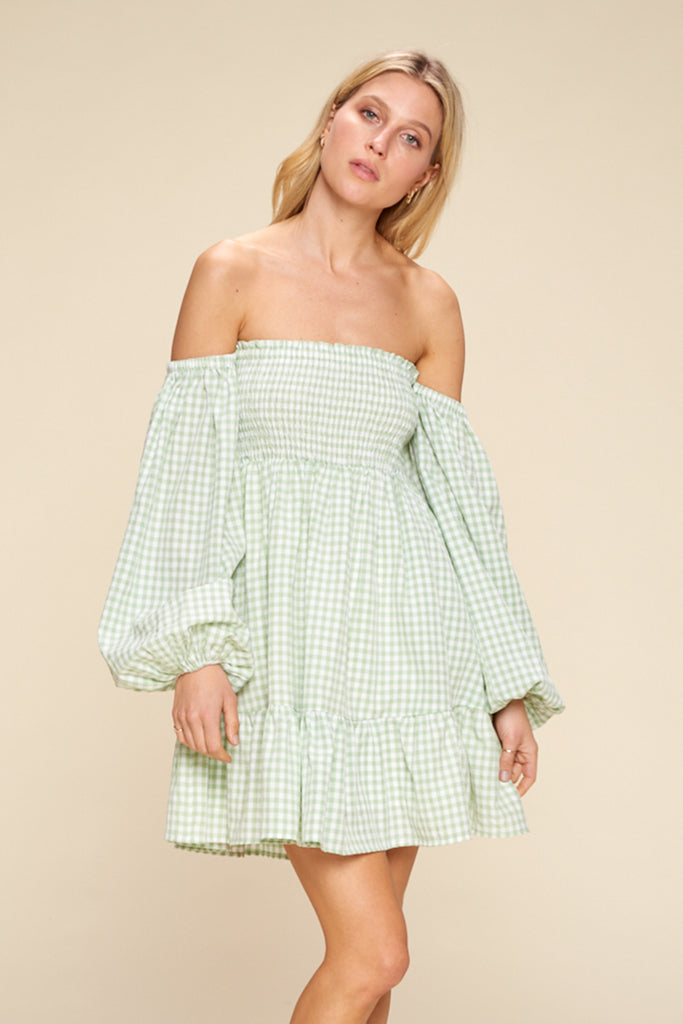 A woman wearing a light green gingham off shoulder mini dress.