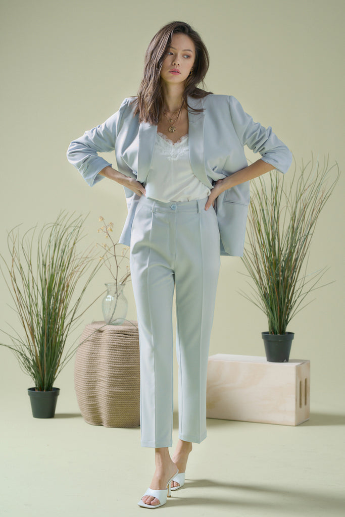 A woman wearing a light blue double breasted blazer and matching trousers.