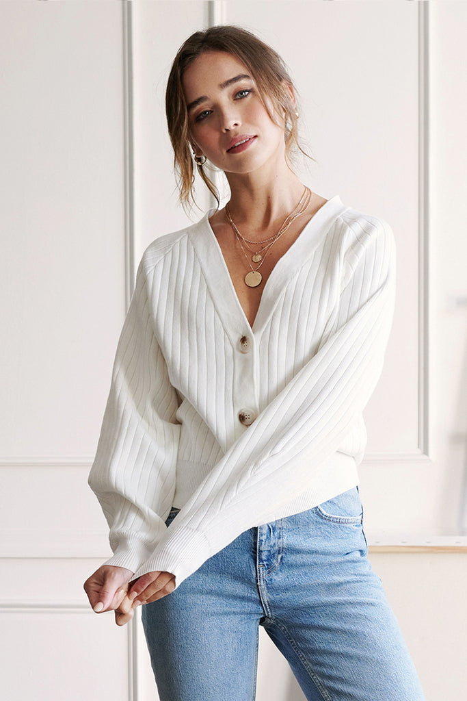 A woman wearing an ivory button front ribbed knit cardigan.