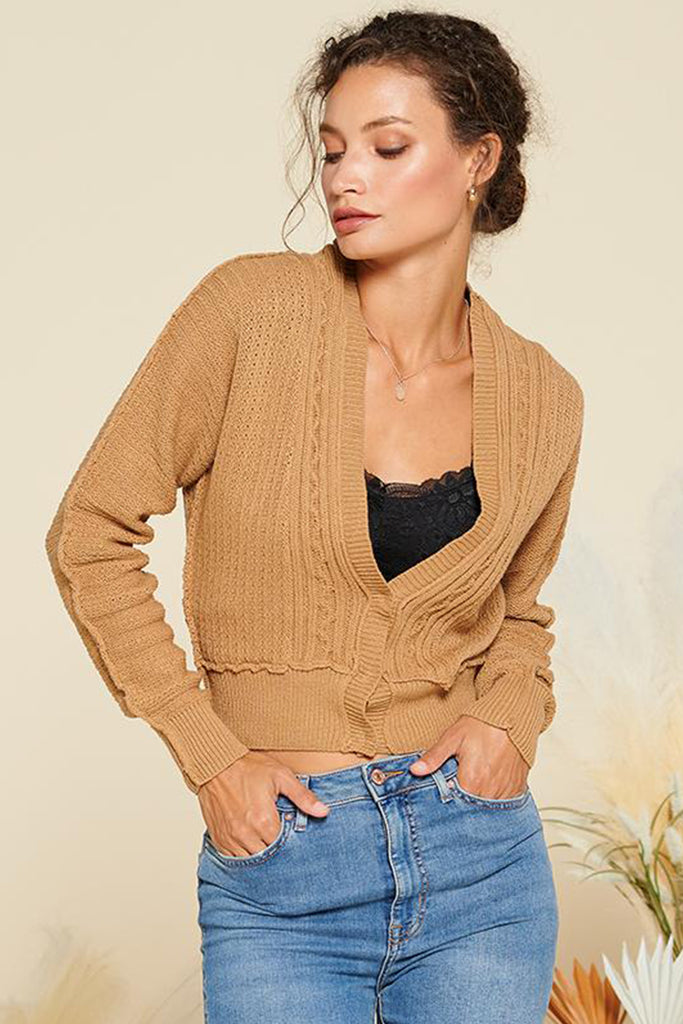 A woman wearing a camel cropped length cable knit cardigan.