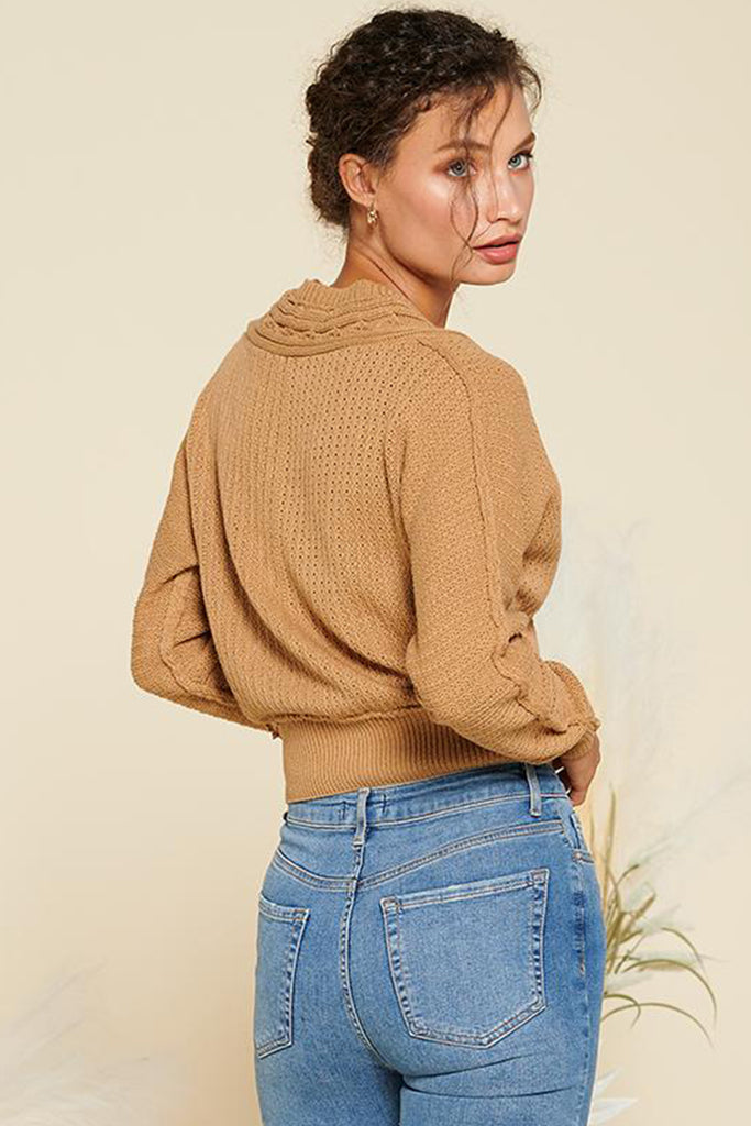 Back side of a camel cropped length cable knit cardigan.