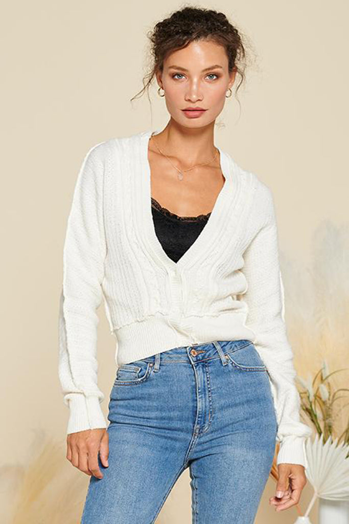 A woman wearing an ivory cropped length cable knit cardigan.