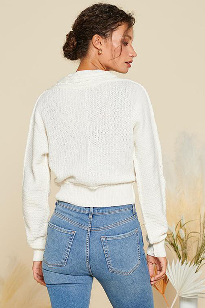 Back side of an ivory cropped length cable knit cardigan.
