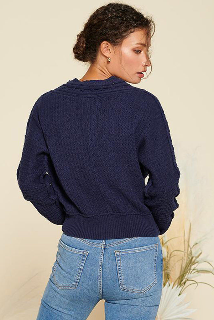 Back side of a navy cropped length cable knit cardigan.