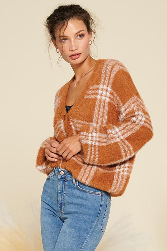 A woman wearing a rust fuzzy plaid cardigan.