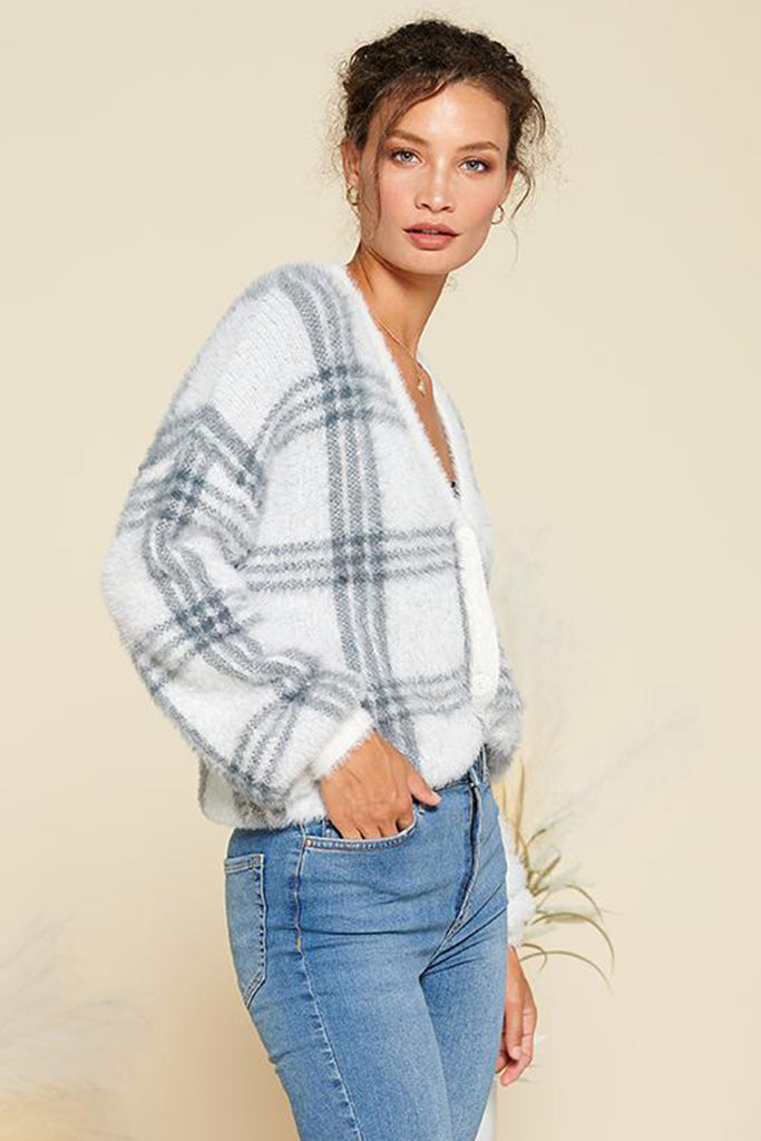 A woman wearing an ivory fuzzy plaid cardigan.