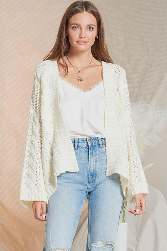 A woman wearing an ivory chunky sweater cardigan.