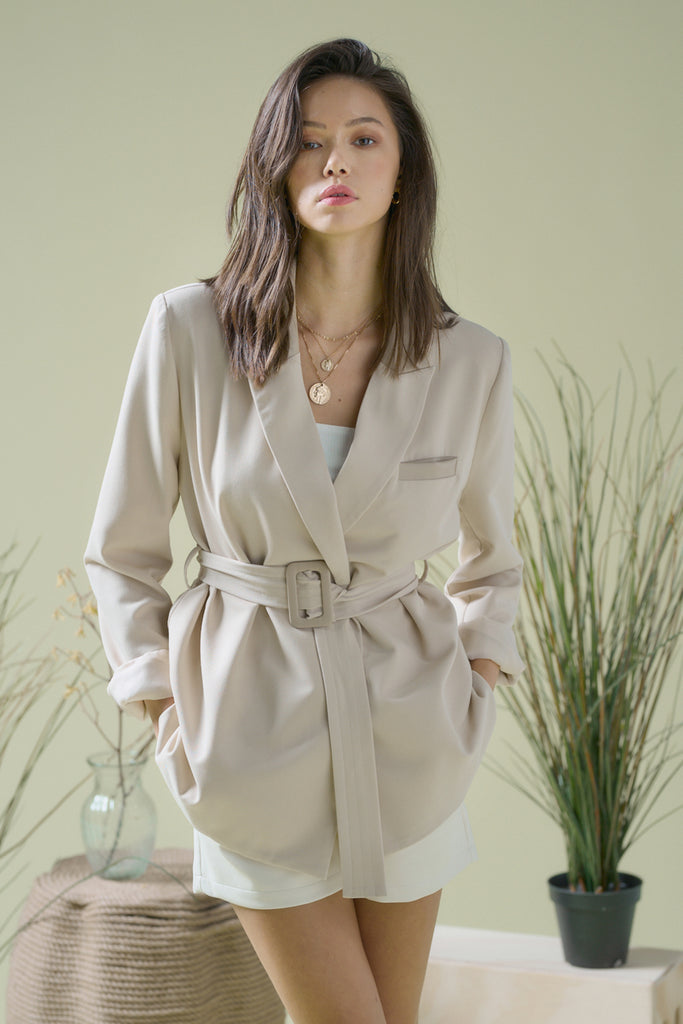 A woman wearing a beige leather-trimmed belted blazer jacket.
