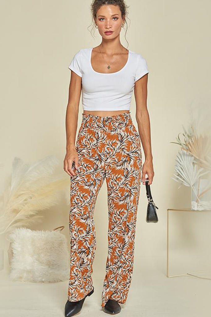 A woman wearing a rust tropical smocked pants.