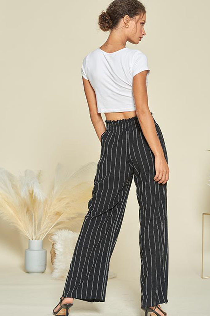 A woman wearing a black striped wide leg pants.