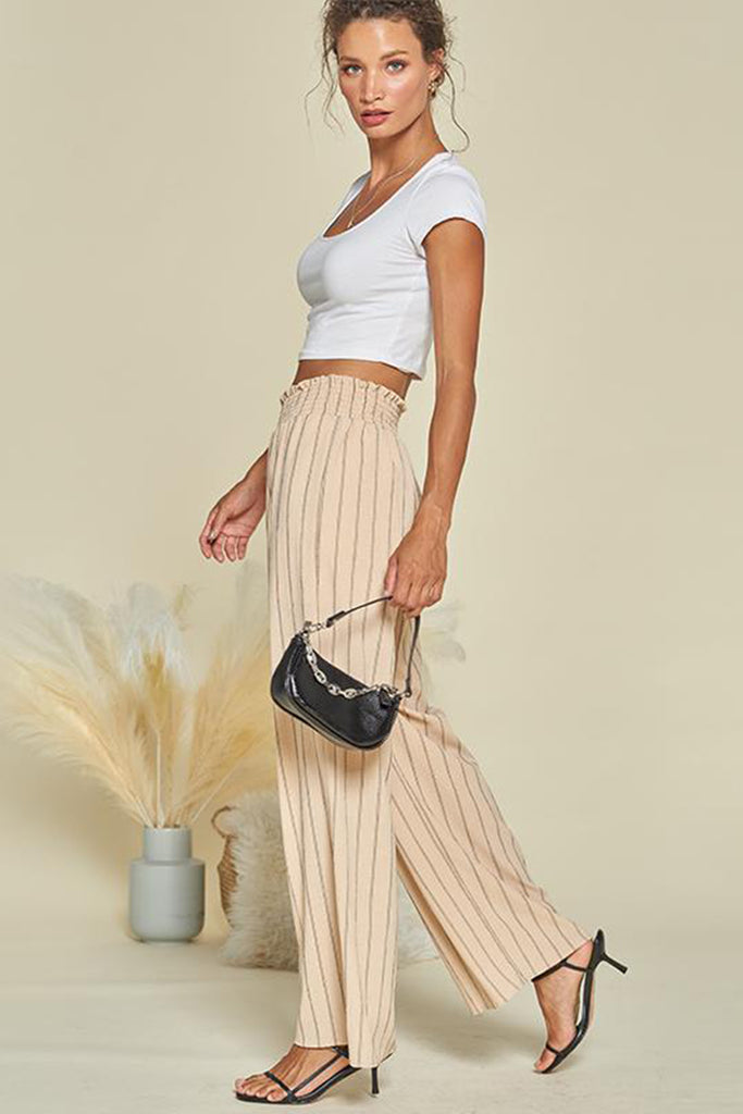 A woman wearing a cream striped wide leg pants.