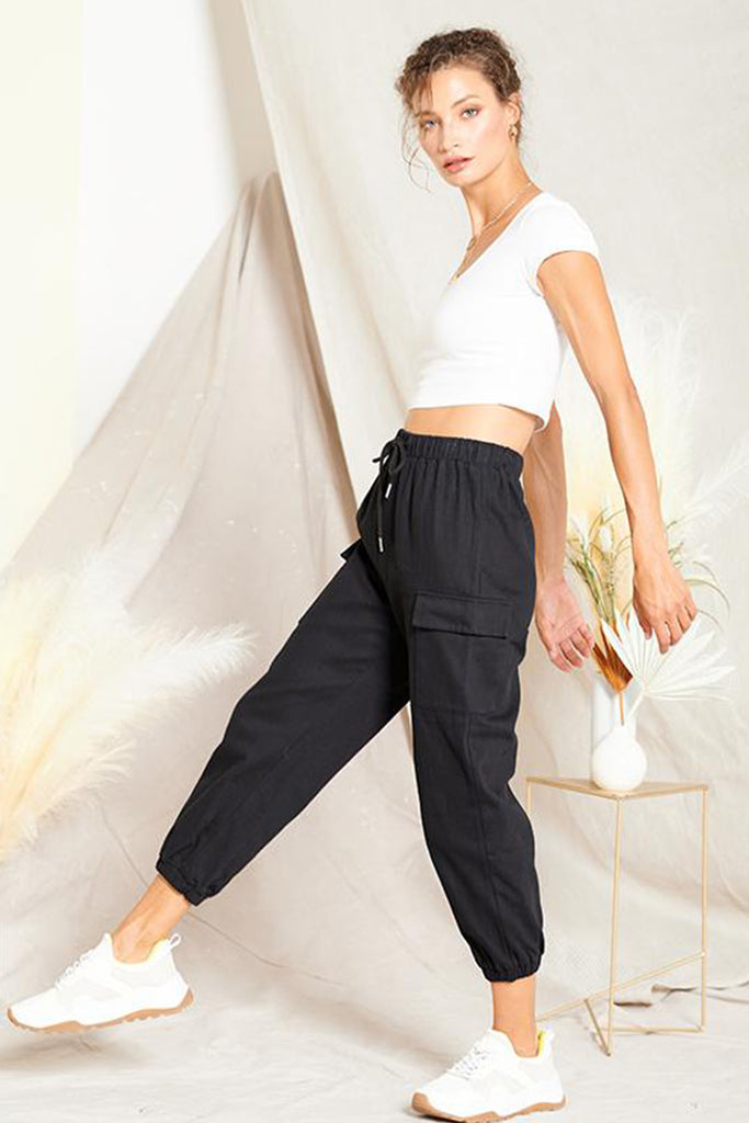 A woman wearing a black cargo jogger pants.