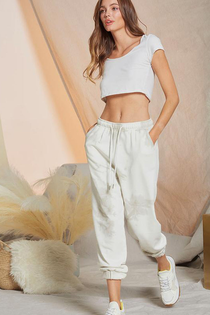 A woman wearing a taupe tie dye jogger pants.