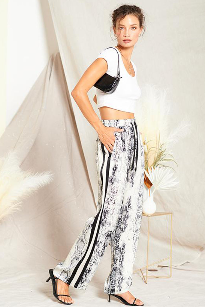 A woman wearing a grey satin snakeskin print pants with contrast stripe panels on both sides.