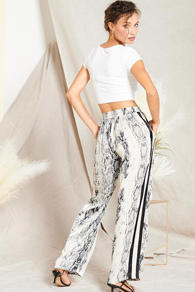 Back side of a grey satin snakeskin print pants with contrast stripe panels on both sides.