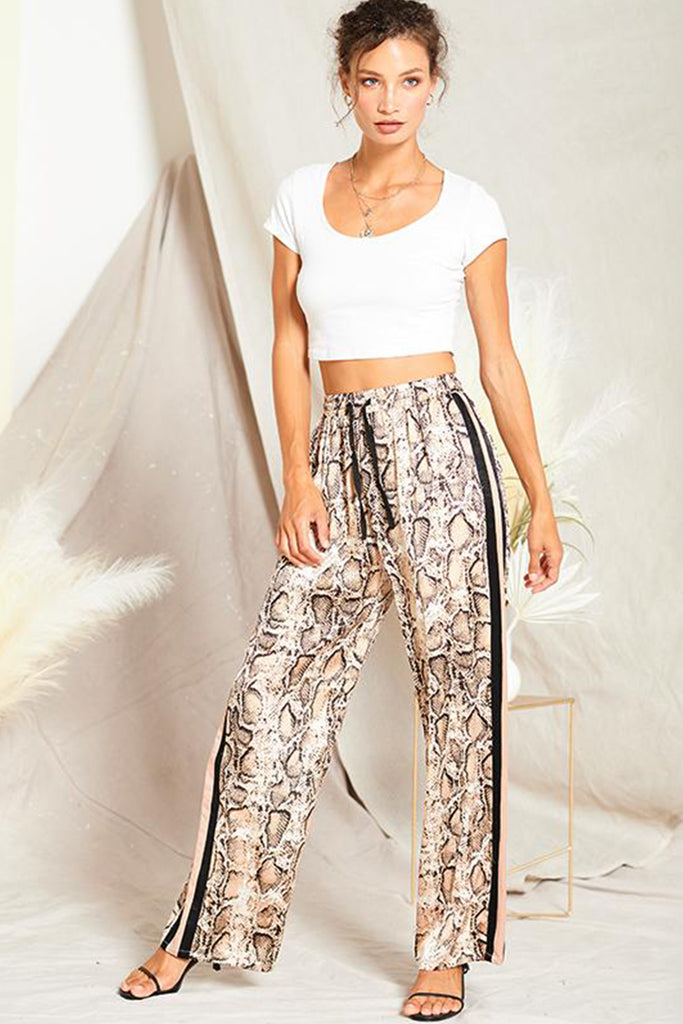 A woman wearing a taupe satin snakeskin print pants with contrast stripe panels on both sides.