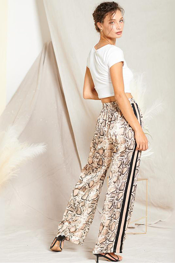 Back side of a taupe satin snakeskin print pants with contrast stripe panels on both sides.