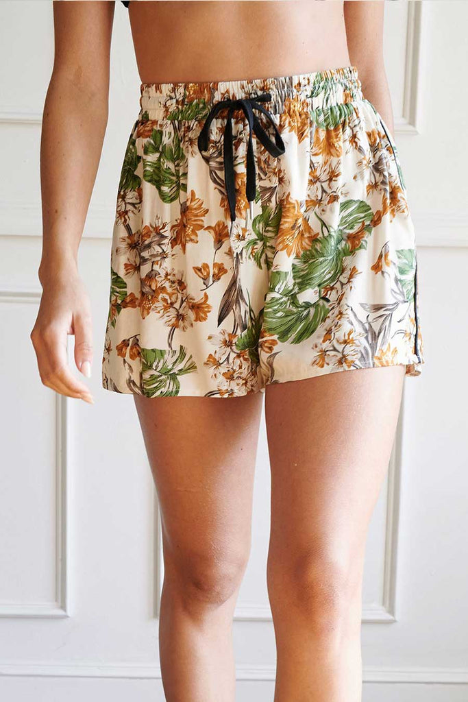 Close up of an ivory satin tropical shorts.