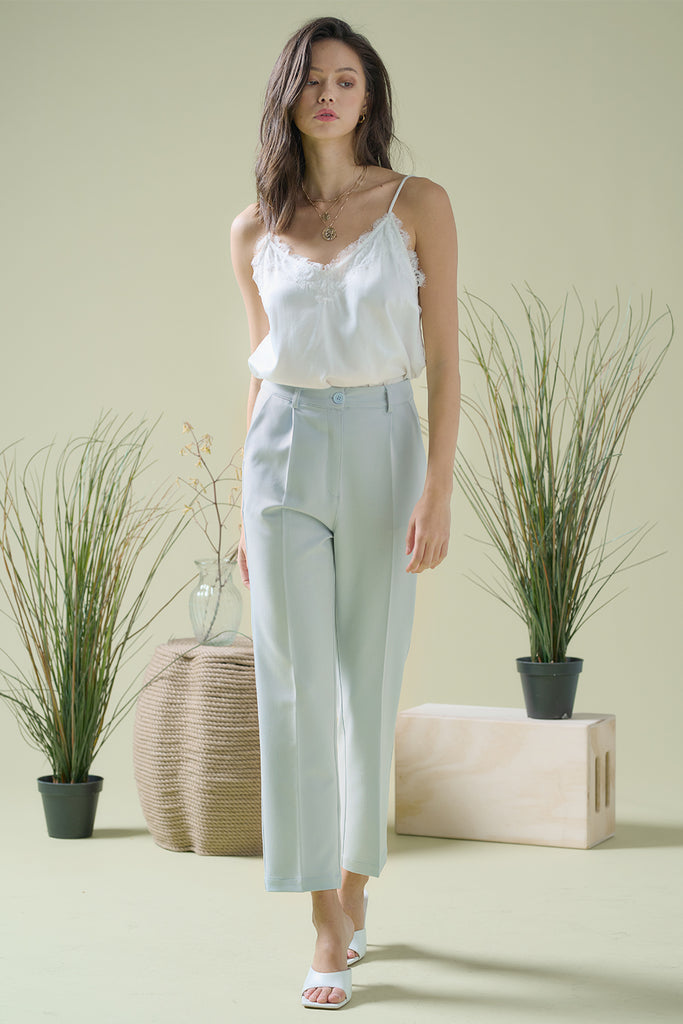 A woman wearing a white satin lace camisole with a light blue straight leg trouser.