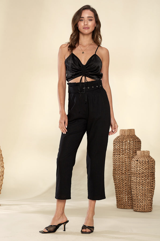 A woman wearing a black paper-bag cropped pants with ruched bandeau top.