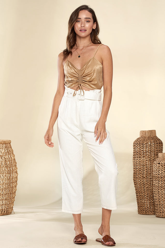 A woman wearing an ivory paper-bag cropped pants with tan ruched bandeau top.