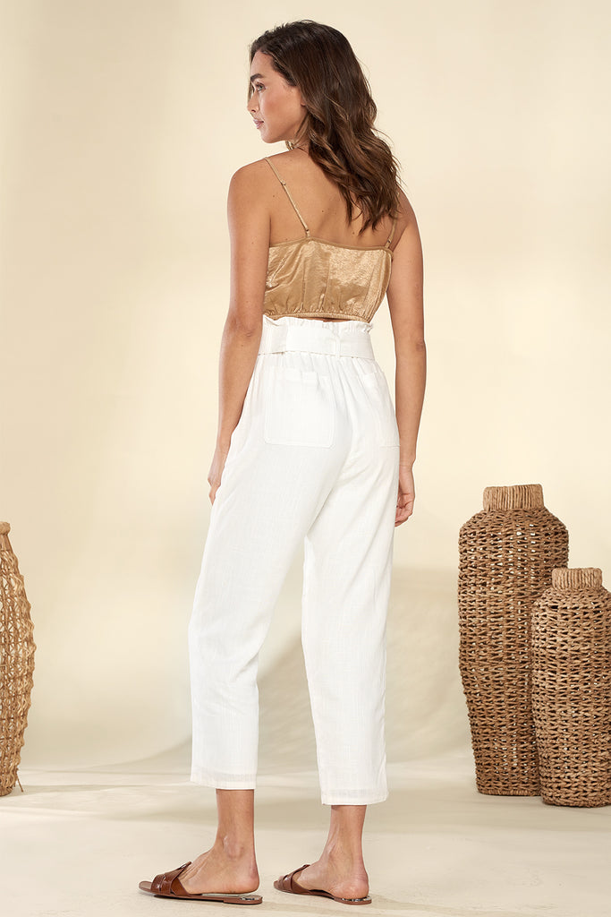 Back side of an ivory paper-bag cropped pants with tan ruched bandeau top.
