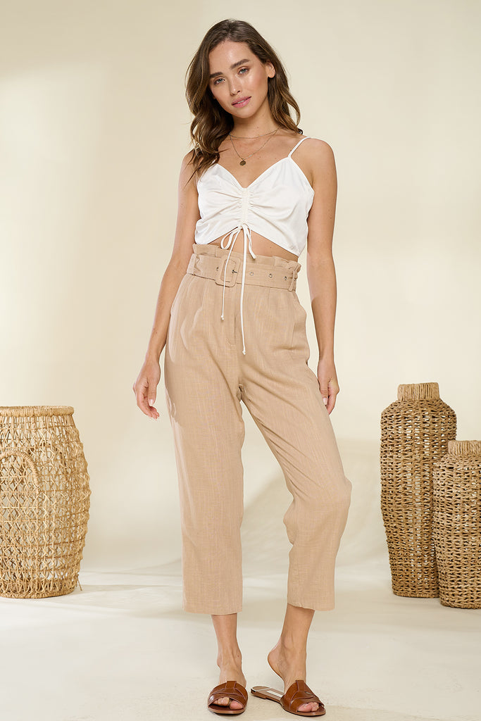 A woman wearing a sand paper-bag cropped pants with ivory ruched bandeau top.