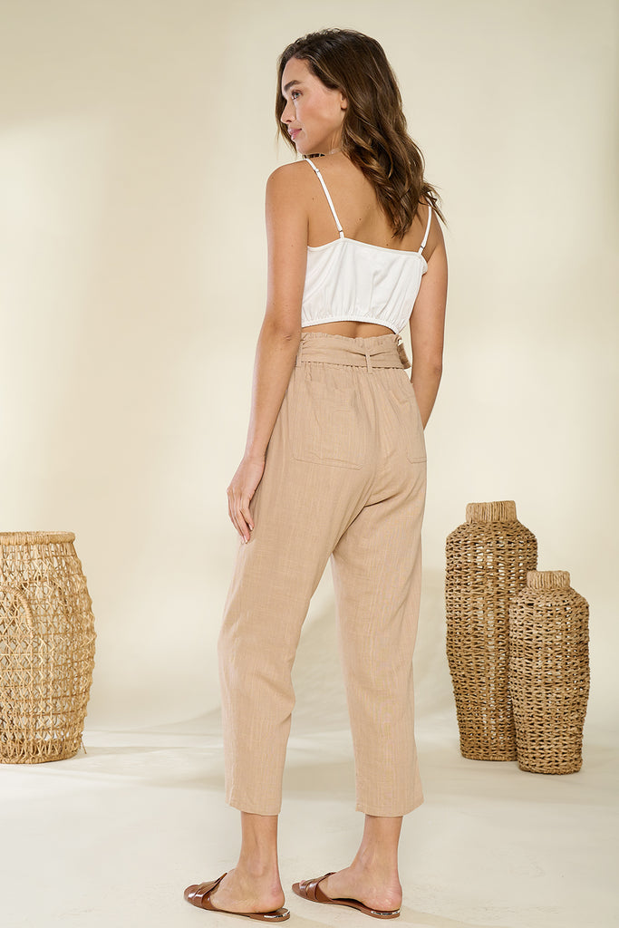 Back side of a sand paper-bag cropped pants with ivory ruched bandeau top.