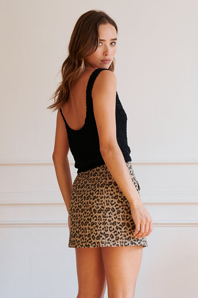 A woman wearing a black knitted tank top and leopard denim mini skirt.
