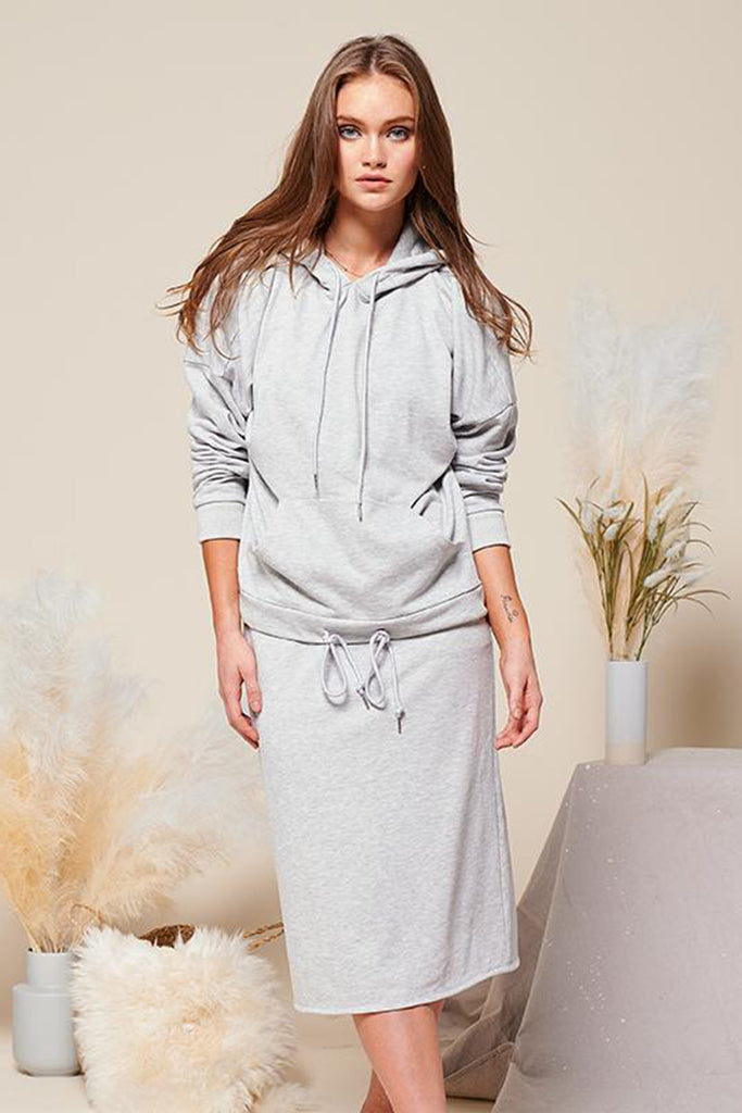 A woman wearing a heather grey knit sweat skirt with matching oversized hoodie.