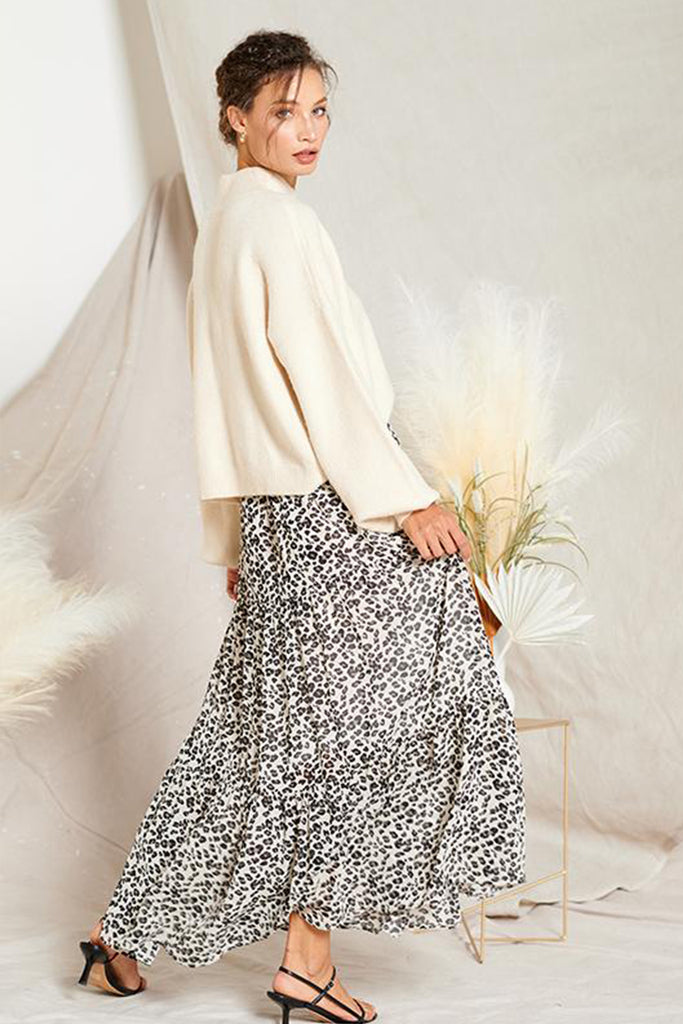 A woman wearing an ivory leopard tiered skirt with an ivory turtleneck sweater.