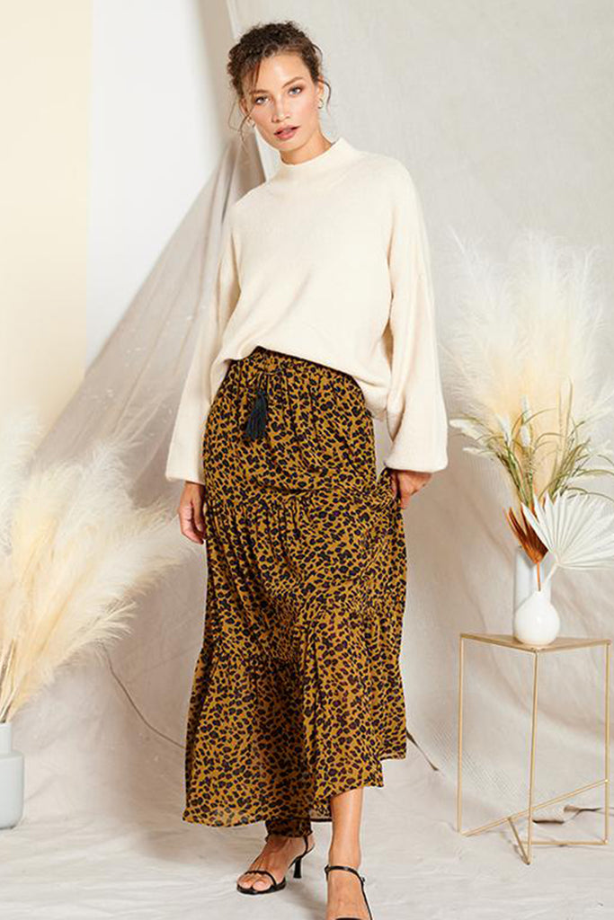 A woman wearing an olive leopard tiered skirt with an ivory turtleneck sweater.