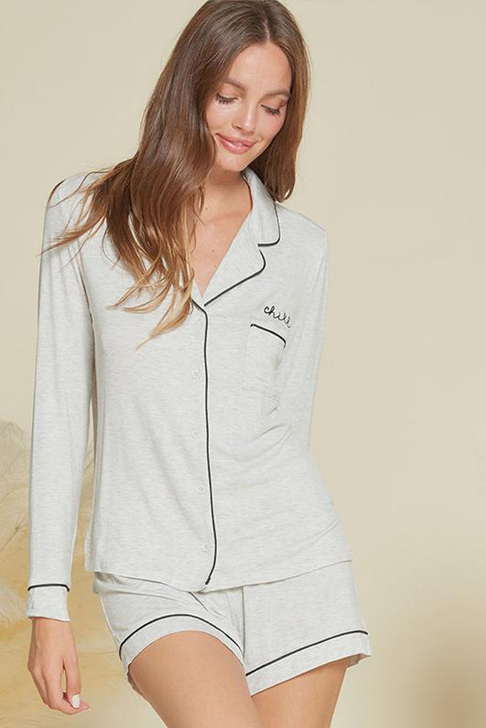 "A woman wearing a light heather grey PJ set with ""chill"" embroidery detail on chest."