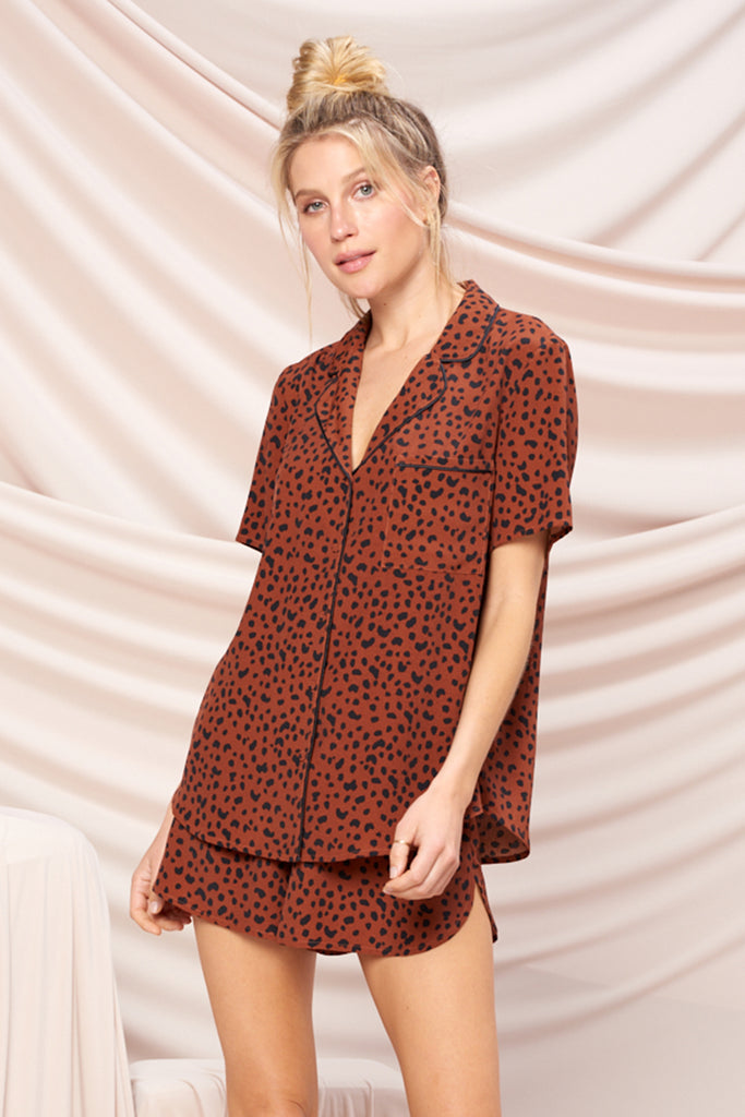 A woman wearing a brown leopard PJ set.