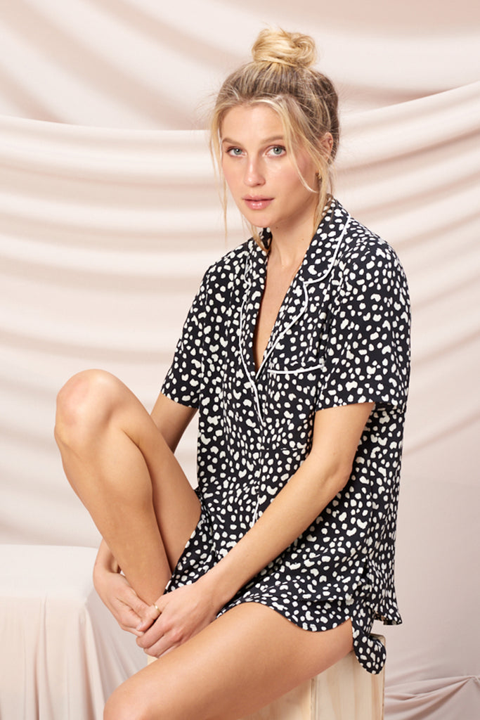 A woman wearing a black leopard PJ set.